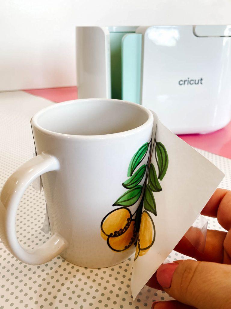 Revealing the colorful design on a mug made with Cricut Mug Press