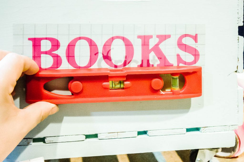 """level lining up the word """"books"""" on crate"""