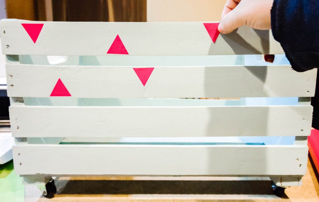 hand applying pink triangles to a book crate