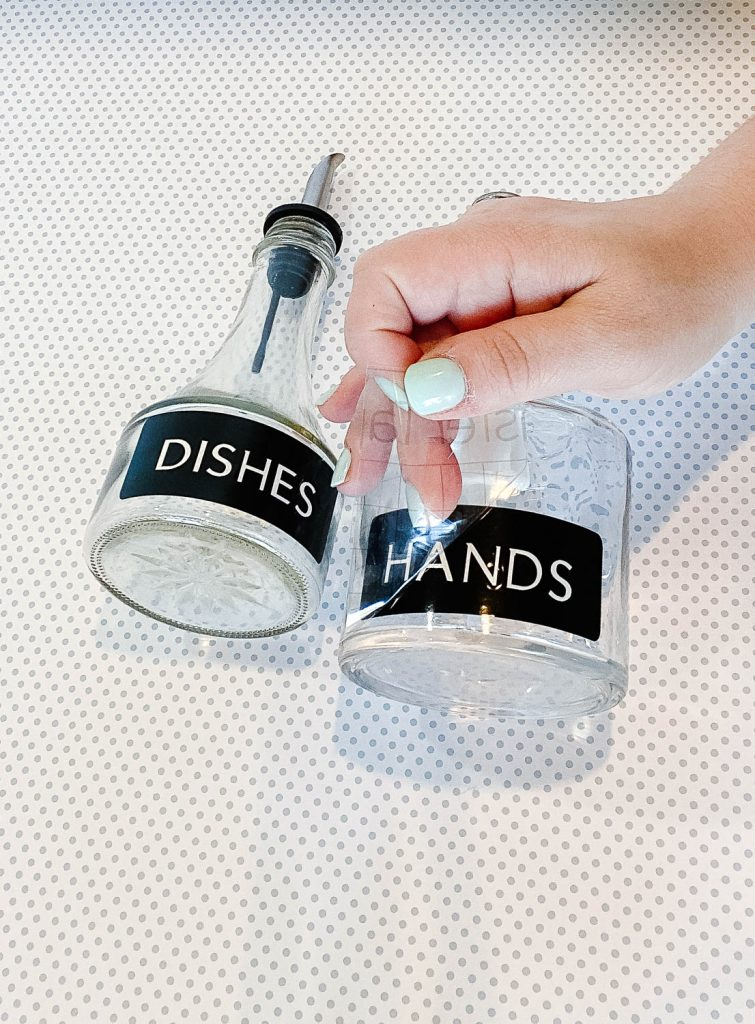 Adding the vinyl labels to the glass bottles.