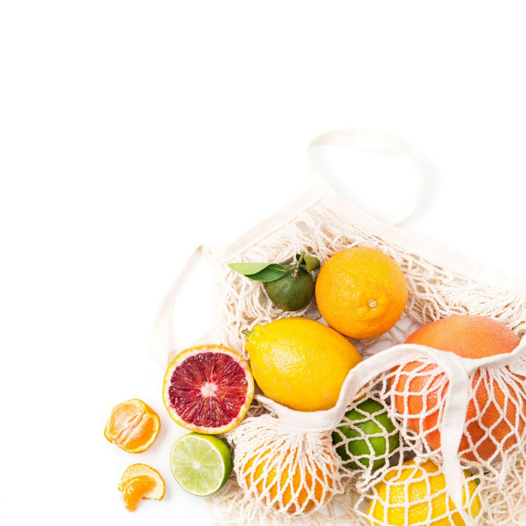 reusable bag of citrus on white background