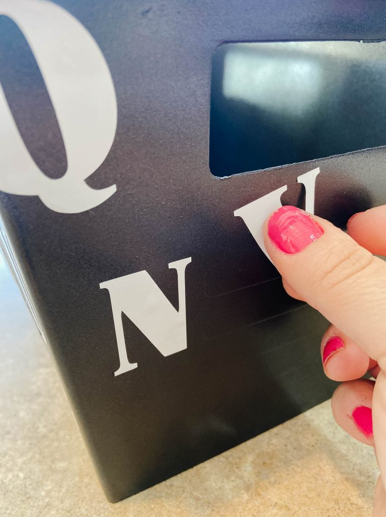close up of thumb pressing a white vinyl sticker onto a black plastic storage bin.
