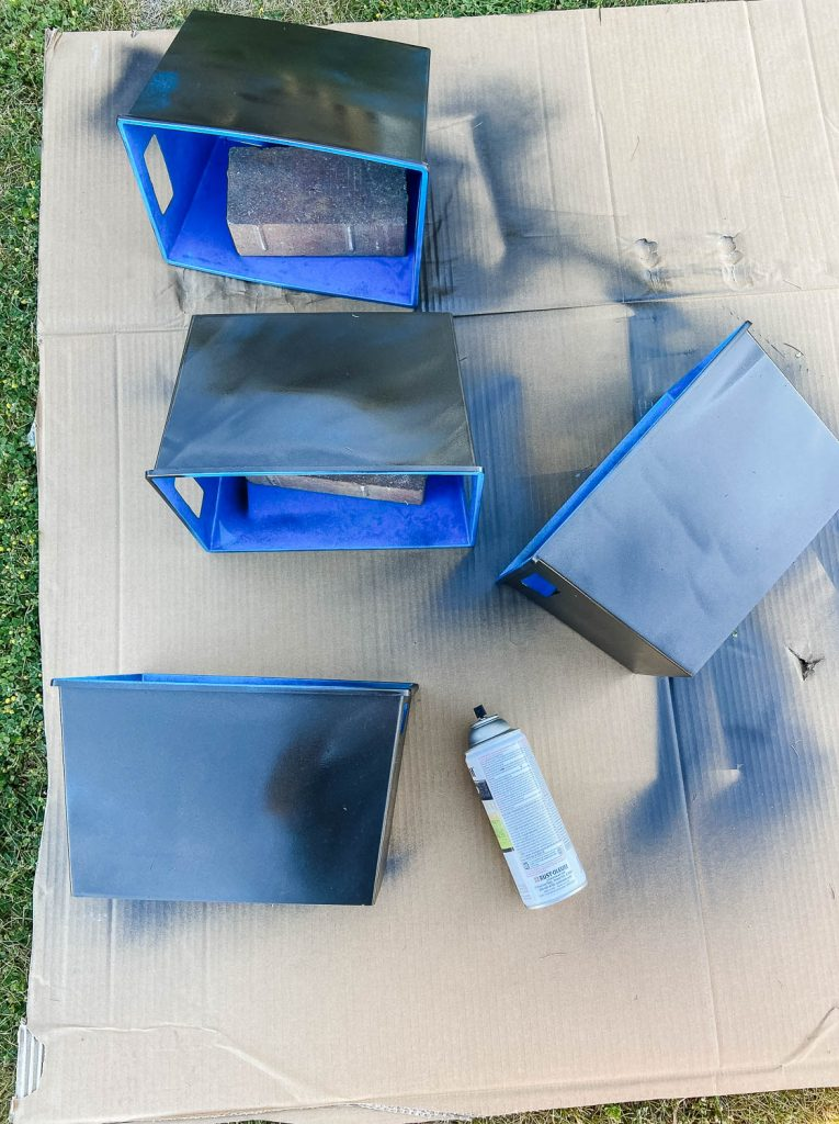 four plastic bins in the process of being spray painted from blue to black.