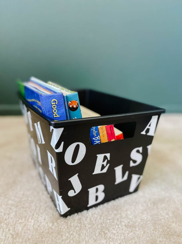 black plastic bin with white letter stickers on it filled with kids books.
