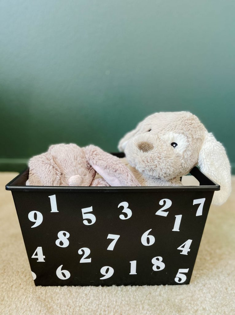 black plastic bin with white numbers filled with stuffed animals.