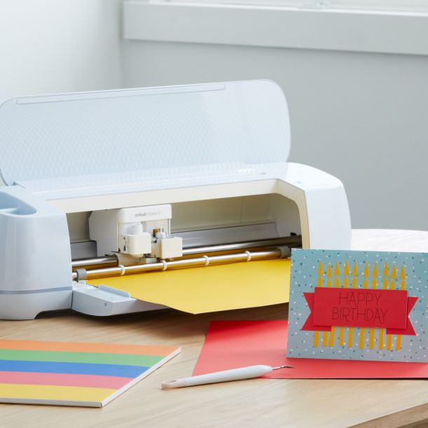 """Cricut Maker cuts paper for a custom birthday card. A card sits up next to it that has candles and says """"Happy Birthday""""  #cricut #cricutmade #cricutmaker3"""