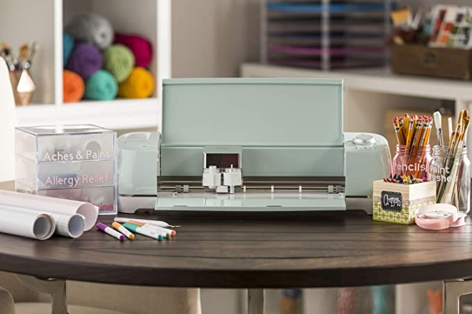Cricut Explore Air 2 on a craft rooom table with pencils, pens, and paint supplies surrounding it.