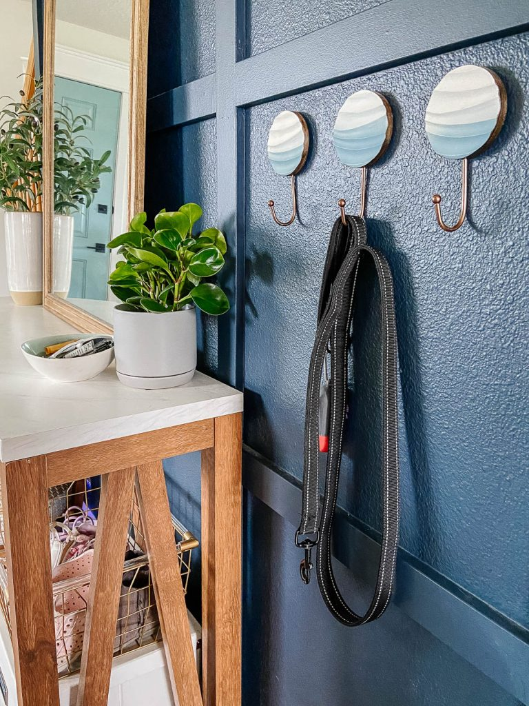 three metal hooks near the entryway table. A dog leash is on one of the hooks.