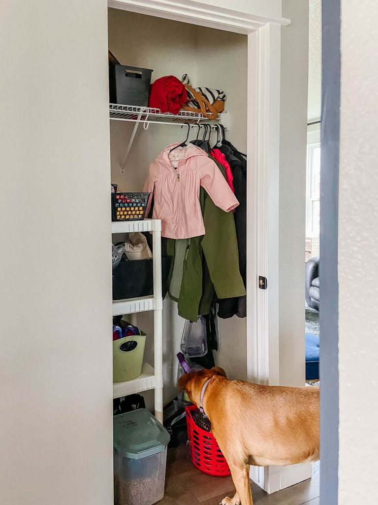 the coat closet with coats hanging up, and a shelving unit for dog items. The family dog is also seen.