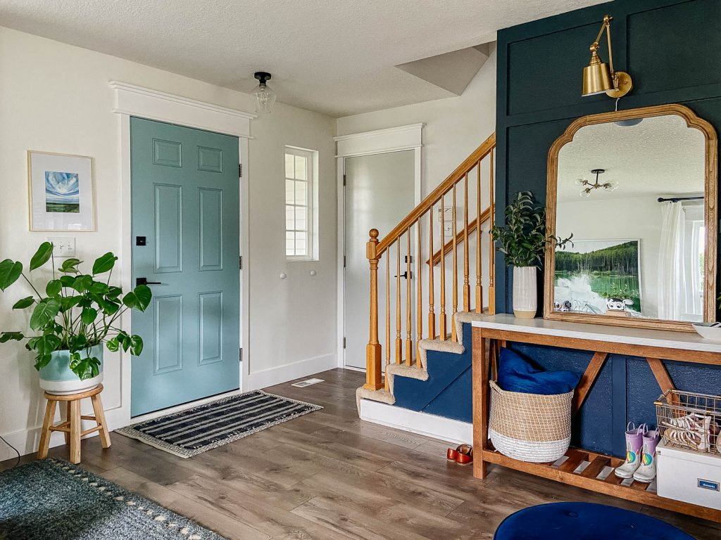 view of the front door and the entryway from inside the home. The entryway has a narrow wooden table with baskets under and a mirror and plants on top.