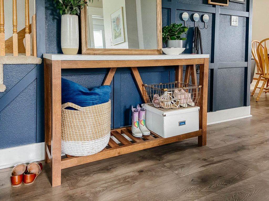 Entryway table with a cloth basket, metal wire basket, and white wooden basket to store shores. The bottom of the table has slots in the shelf.
